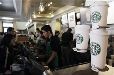 Employees of Starbucks Corp work inside the branch in Antiguo Cuscatlan, some 8 km (4 miles) southwest of San Salvador November 5, 2010. REUTERS/Luis Galdamez