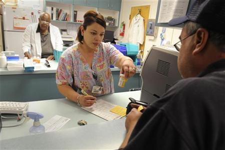 Pharmacy tech Maria Santoyo (C) works in Clinica Sierra Vista's Lamont Community Health center in Bakersfield, California October 20, 2009. REUTERS/Phil McCarten