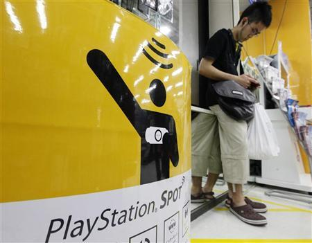 A man plays his Sony PlayStation portable console at a PlayStation wireless spot in an electronic shop in Tokyo May 15, 2011. REUTERS/Kim Kyung-Hoon