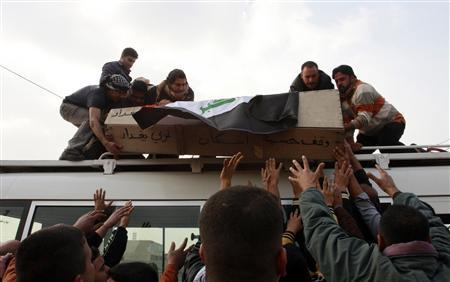 Relatives place the coffin of Abdul Jabar Mukhtar, an employee at the Foreign Affairs Ministry, on a bus during a funeral in Baghdad, in a January 2011 file photo. REUTERS/Ahmed Malik/Files
