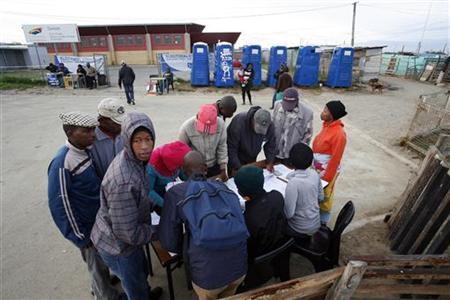 People check for their names before casting their votes during the South African municipal elections in Cape town May 18 2011. REUTERS/Mark Wessels
