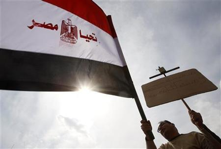 An Egyptian holds up a Koran on a cross and an Egyptian flag that reads ''Live Egypt'' during a rally to demonstrate the unity between Muslims and Christians at Tahrir Square in Cairo March 11, 2011. REUTERS/Amr Abdallah Dalsh