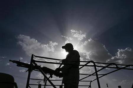 A paramilitary soldier is seen silhouetted against the sun as he keeps guard at the site where security forces killed five would-be suicide bombers on the outskirts of Quetta May 17, 2011. REUTERS/Naseer Ahmed