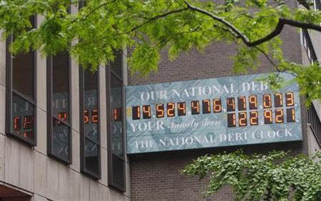 The National Debt Clock, which displays the current United States gross national debt and each American family's share, hangs on a wall next to an office for the Internal Revenue Service near Times Square, in New York, May 16, 2011. REUTERS/Chip East