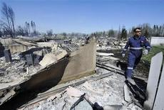 <p>A fire-fighter from the Strathcona fire department searches for spot fires in a destroyed neighborhood in Slave Lake, Alberta May 16, 2011. REUTERS/Todd Korol</p>
