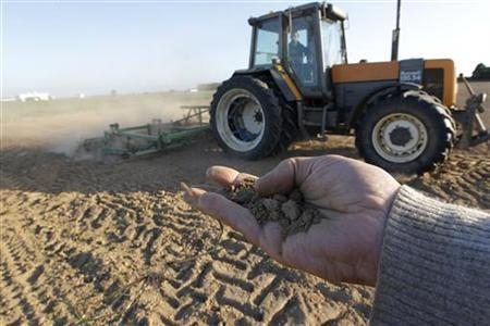 A French farmer holds dry earth in his hand as a tractor works in a field in Blecourt, northern France, May 12, 2011. REUTERS/Pascal Rossignol