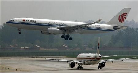 An Air China Airbus A330-243 aeroplane descends to land as a China Eastern plane waits on the tarmac at Beijing airport May 11, 2011. REUTERS/David Gray