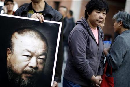 A supporter of Chinese artist Ai Weiwei holds a picture of him in Shanghai, November 7, 2010. REUTERS/Carlos Barria