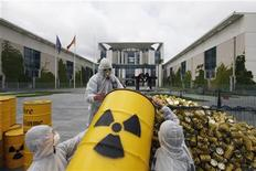 "<p>""Tollwood"" environmental activists empty symbolic nuclear waste barrels into a cage outside the Chancellery to protest against the government's nuclear energy policy calling for a swift nuclear energy exit in Berlin May 16, 2011. REUTERS/Thomas Peter</p>"
