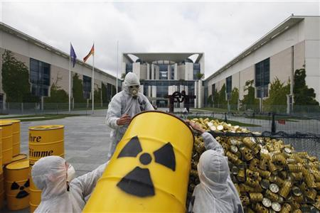 ''Tollwood'' environmental activists empty symbolic nuclear waste barrels into a cage outside the Chancellery to protest against the government's nuclear energy policy calling for a swift nuclear energy exit in Berlin May 16, 2011. REUTERS/Thomas Peter