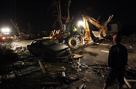 Ted Grabenauer, of Joplin, looks at heavy duty equipment operators clear the street in the early morning hours in Joplin, Missouri May 23, 2011, the day after a devastating tornado hit the town. REUTERS/Mike Stone