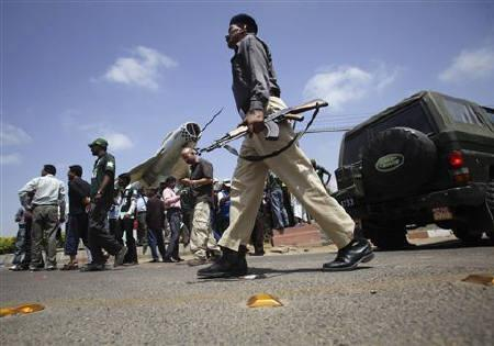 A policeman walks near the front gates of the Mehran naval aviation base after troops ended operations against militants in Karachi May 23, 2011. REUTERS/Akhtar Soomro