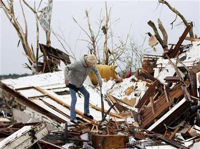 A woman removes a rifle from the debris of a destroyed home after a devastating tornado hit Joplin, Missouri May 23, 2011. REUTERS/Mike Stone