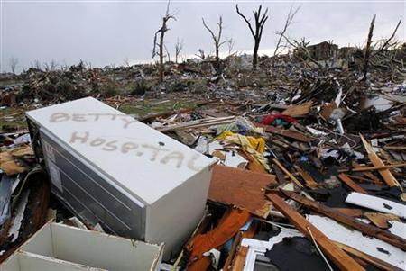 A refrigerator baring a woman's name and the word 'hospital' lay strewn about with the debris of a neighborhood totally destroyed by a devastating tornado in Joplin, Missouri May 23, 2011. REUTERS/Mike Stone )