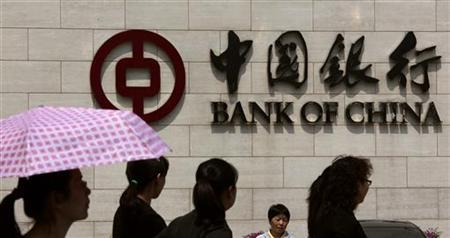 Pedestrians walk past the headquarters of the Bank of China in central Beijing April 28, 2011. REUTERS/David Gray