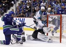 <p>Vancouver Canucks left wing Alex Burrows (14) shoots the puck past San Jose Sharks goalie Antti Niemi (31) for a first period goal during Game 5 of their NHL Western Conference Final hockey playoff in Vancouver, British Columbia May 24, 2011. REUTERS/Ben Nelms</p>