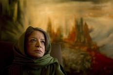 <p>Painter Iran Darroudi poses for a portrait in front of one of her paintings at her home in Tehran April 12, 2011. REUTERS/Caren Firouz</p>