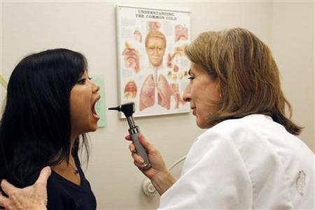 Bonnary Lek, a manager at Discovery Communications headquarters, is examined by Discovery Wellness Center Medical Director Liz Sequeira during an appointment at the clinic in Silver Spring, Maryland December 3, 2009. REUTERS/Jim Bourg