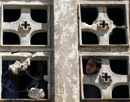 A Coptic Christian boy looks out of the Saint Mary Church which was set on fire during clashes between Muslims and Christians on Saturday in the heavily populated area of Imbaba in Cairo May 8, 2011. Egypt's prime minister called an emergency cabinet meeting on Sunday after 10 people died in bloody clashes in a Cairo suburb over the conversion of a Christian woman to Islam. REUTERS/Asmaa Waguih