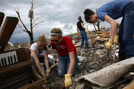 Volunteers dig through the rubble of a home, which is destroyed by a tornado in Joplin, Missouri May 25, 2011. REUTERS/Eric Thayer