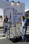 """<p>Мужчины везут оборудование для поготовки к проведению саммита """"Большой восьмерки"""" в Довиле, 25 мая 2011 года. Лидеры стран """"Большой восьмерки"""" соберутся в прибрежном городке Франции в четверг, чтобы обсудить поддержку новых демократических режимов в арабском мире. REUTERS/Jean-Paul Pelissier</p>"""