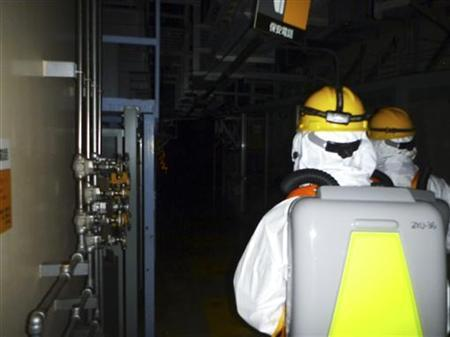 Workers wearing protective suits enter the Tokyo Electric Power Co. (TEPCO)'s Fukushima Daiichi nuclear power plant No.2 reactor building in Fukushima Prefecture, in this handout photo taken on May 18 and released by TEPCO on May 19, 2011. REUTERS/Tokyo Electric Power Co/Handout