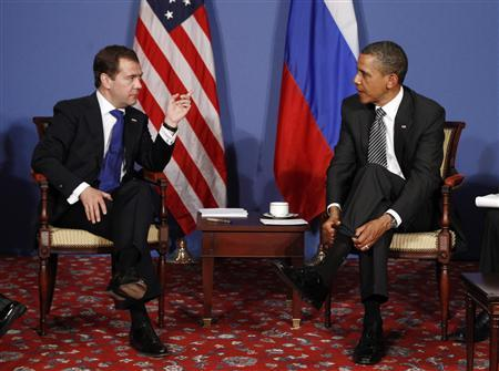 President Barack Obama (R) pulls up his socks as Russian President Dmitry Medvedev speaks during the G8 Summit in Deauville May 26, 2011. REUTERS/Kevin Lamarque
