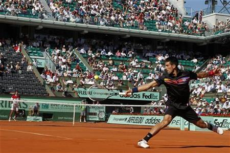 Novak Djokovic of Serbia returns the ball to Victor Hanescu of Romania during the French Open tennis tournament at the Roland Garros stadium in Paris May 25, 2011. REUTERS/Thierry Roge