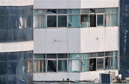 A man stands next to the broken windows after an explosion at the procuratorate building in Fuzhou, Jiangxi province May 26, 2011. REUTERS/Stringer