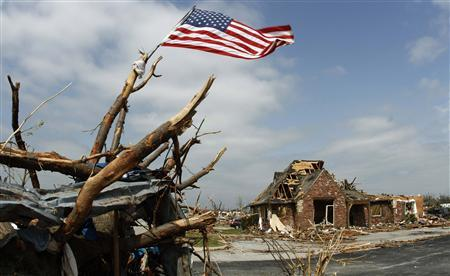 A United States flag tied to a tree branch waves in the wind over a business building destroyed by a tornado in Joplin, Missouri, May 24, 2011. REUTERS/Ed Zurga