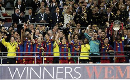 Barcelona's Eric Abidal (R) lifts the trophy alongside jubilant teammates after their Champions League final soccer match victory against Manchester United at Wembley Stadium in London May 28, 2011. REUTERS/Darren Staples