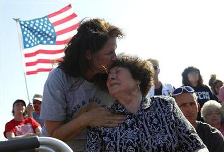 Kathy White consoles her sister Joanne Molinar at a ceremony marking a week since a tornado hit Joplin, Missouri May 29, 2011.REUTERS/Eric Thayer
