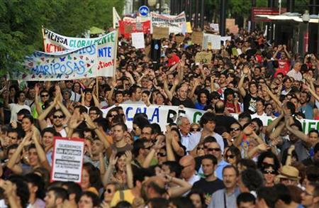 Protesters hold banners and shout slogans in Seville May 29, 2011, in support of demonstrators gathered at Barcelona's Plaza Catalunya. REUTERS/Javier Diaz