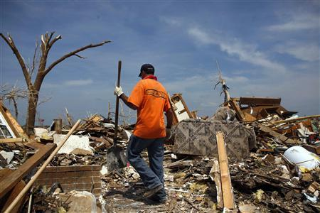 A man looks through a destroyed home in Joplin, Missouri May 30, 2011. A May 22, 2011 tornado in Joplin, a city of 50,000 in southwestern Missouri, was the deadliest single twister in the United States since 1947. REUTERS/Eric Thayer