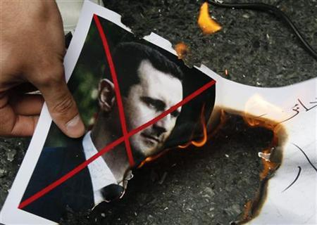 A demonstrator sets fire to a picture of Syria's President Bashar al-Assad during a demonstration against the government of Syria, outside the Syrian consulate in Istanbul, May 13, 2011. REUTERS/Osman Orsal