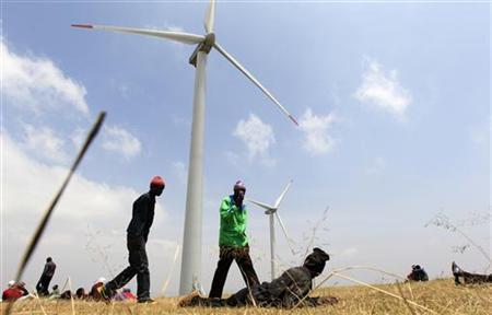 People walk near power-generating wind turbines at the Kenya Electricity Generating Company (KenGen) station in Ngong hills, about 22 km (14 miles) southwest of Kenya's capital Nairobi, September 8, 2010. REUTERS/Thomas Mukoya