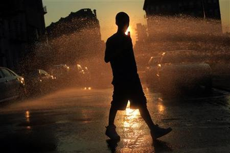 A boy walks near water spraying from an open fire hydrant in the Williamsburg neighborhood of Brooklyn, New York July 5, 2010.