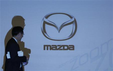 A man walks past a Mazda Motor Corp logo projected on a screen at a news conference in Tokyo April 27, 2010. REUTERS/Yuriko Nakao