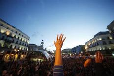 <p>Demonstrators raise their hands as they listen to a speaker at Madrid's landmark Puerta del Sol May 31, 2011. REUTERS/Susana Vera</p>