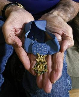 Walter Ehlers, a 90-year-old Medal of Honor recipient who took part in the D-Day invasion of World War II, holds the medal in his hands in his home in Buena Park, California June 2, 2011. REUTERS/Alex Gallardo