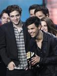 """<p>Taylor Lautner (en el centro) recibe el premio a mejor película junto al elenco de """"The Twilight Saga: Eclipse"""" en los premios MTV Movie Awards 2011 en Los Angeles, 5 de junio del 2011. Los premios MTV Movie Awards se convirtieron en publicidad gratis para la franquicia de películas """"Twilight"""". Por tercer año consecutivo, la película de romance entre una mortal y un vampiro fue escogida como el mejor filme del año en una ceremonia alegre, a veces subida de tono, que honra a las películas más vistas de Hollywood. REUTERS/Mario Anzuoni.</p>"""