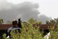 <p>Журналист снимает дым над Триполи с крыши отеля 7 июня 2011 года. Серия взрывов произошла во вторник в Триполи, ответственность за которые ливийские власти возложили на авиацию НАТО. В последние дни альянс активизировал свои усилия в североафриканской стране и наносит удары с перерывом всего в несколько часов. REUTERS/Ahmed Jadallah</p>