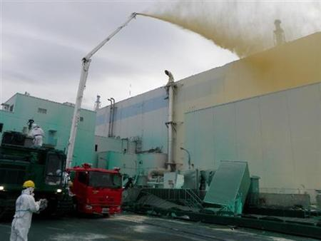 Workers spray a dust inhibitor at Tokyo Electric Power Co.(TEPCO)'s Fukushima Daiichi nuclear power plant in Fukushima, northern Japan, in this handout photo taken May 27, 2011 and released by TEPCO on May 28, 2011. REUTERS/Tokyo Electric Power Co/Handout