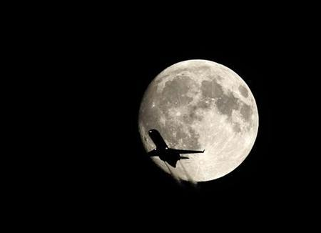 A plane flies past the full moon over Budapest September 25, 2007. REUTERS/Viktor Ufo