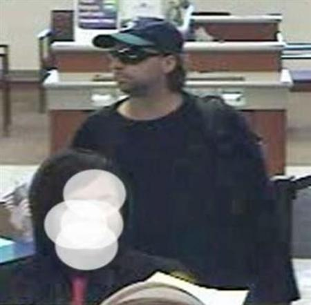A surveillance image released by the FBI shows a man with a mullet and a Seattle Mariners cap at the Fifth Third Bank in Columbus Ohio on May 18, 2011. Reuters/FBI