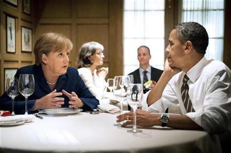 German Chancellor Angela Merkel speaks to U.S. President Barack Obama during a private dinner at the 1789 restaurant in Washington June 6, 2011. REUTERS/Jesco Dezel/Bundesregierung/Pool
