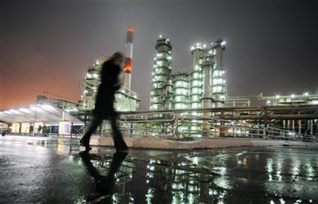 A man walks in front of the Novokuibyshevsk refinery near the city of Samara, October 28, 2010. REUTERS/Nikolay Korchekov