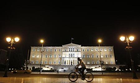 A man rides his bicycle past the parliament building in Athens May 9, 2011. REUTERS/Yiorgos Karahalis
