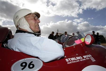 Former Formula One world champion Stirling Moss of Britain sits in a Maserati replica Formula One car during the Australian Grand Prix at the Albert Park race track in Melbourne April 2, 2006. REUTERS/Mark Horsburgh