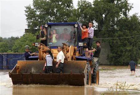 Rescue staff transfers residents to a safe area with a forklift in flooded Xiushui county, Jiangxi province June 10, 2011. Reuters/Stringer